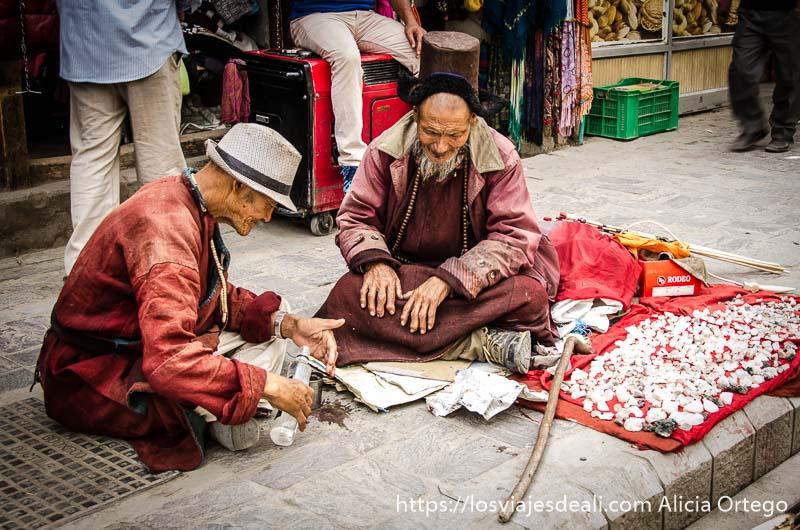 dos hombres tibetanos sentados en el suelo de la calle uno anciano con gorro negro y barba blanca