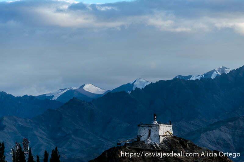 el pico más alto cerca de Leh en el horizonte con nieve, y un pequeño monasterio en una montaña anterior