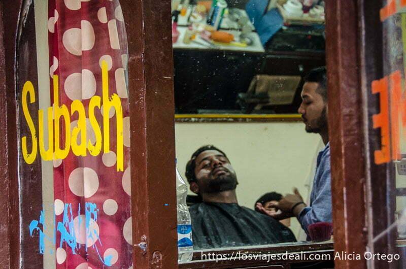 barbero tradicional arreglando barba a un cliente que mira a través del espejo la calle en Leh