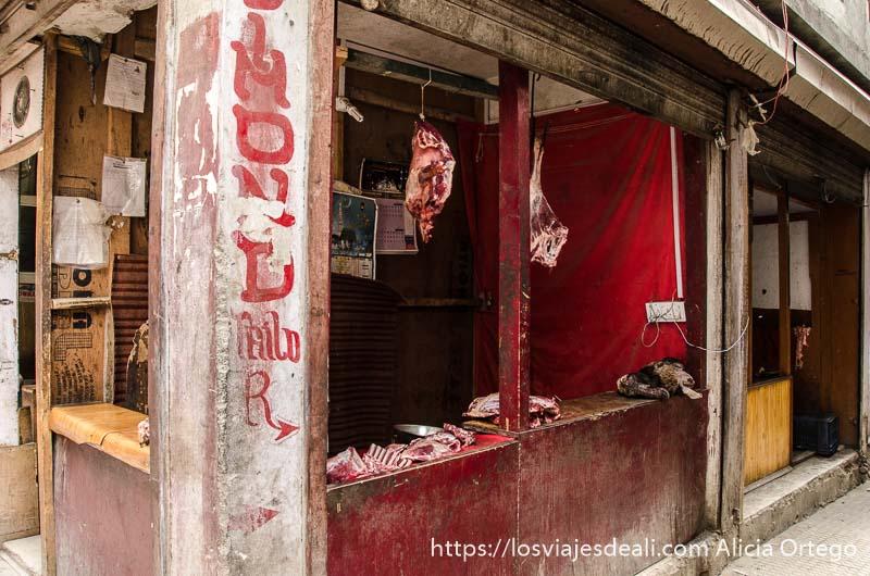 carnicería con piezas de carne colgando en leh