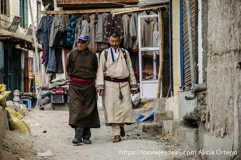 dos hombres tibetanos caminan por las calles del viejo leh con su traje típico
