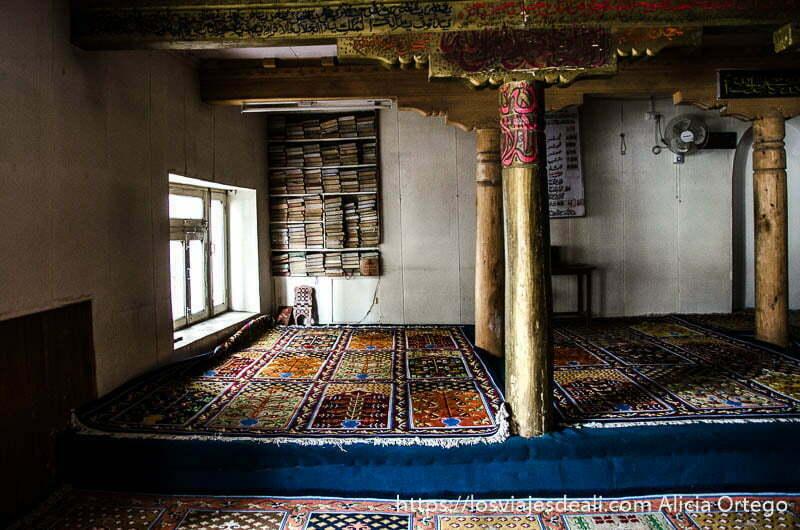 sala de oración de mezquita de leh con alfombras en el suelo y columnas de madera pintadas