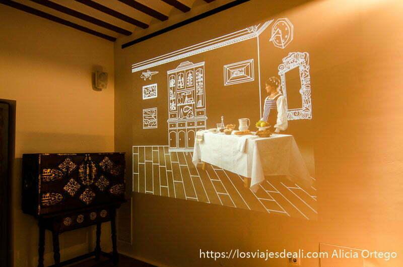proyección en la pared donde se ve a una mujer ante una mesa con alimentos en el museo del hidalgo de alcázar de san juan
