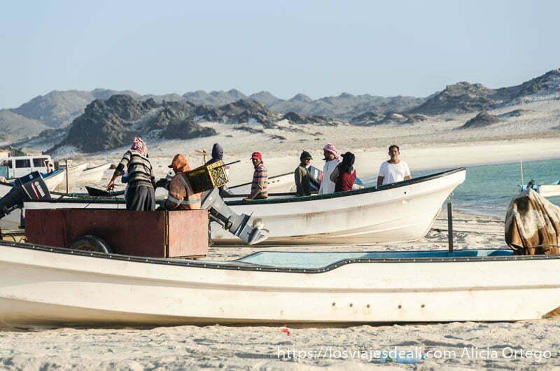 grupo de pescadores recogiendo sus cosas en las barcas de pesca en la playa masirah