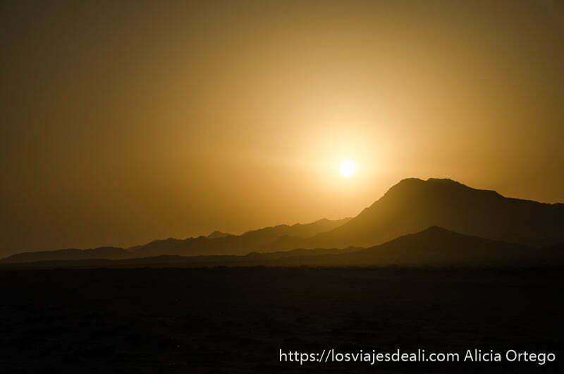 sol poniéndose tras las montañas recortadas en negro en isla masirah