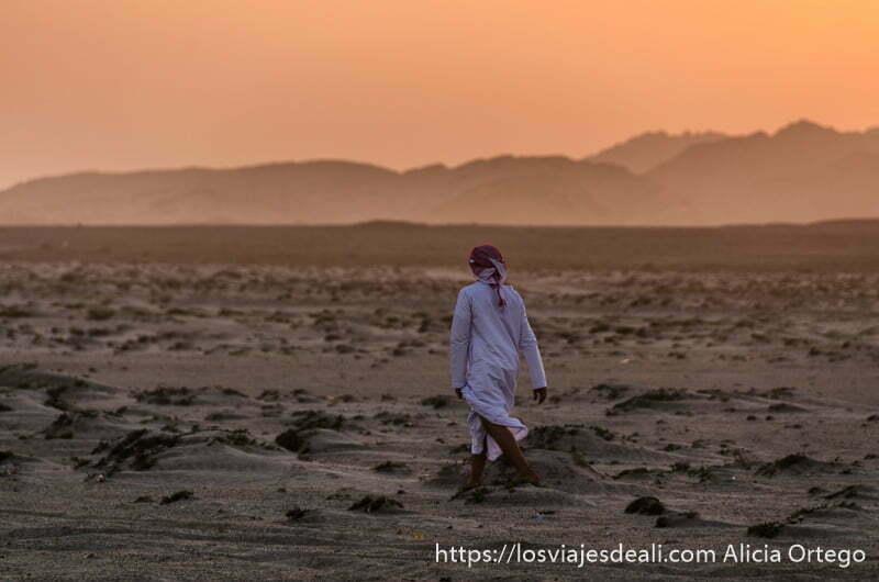 Ali caminando por la arena con montañas al fondo y cielo rojo por atardecer en masirah