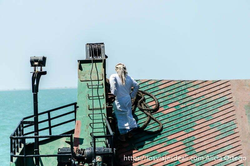 hombre omaní con su vestimenta típica subido a la plataforma del ferry mirando al mar masirah