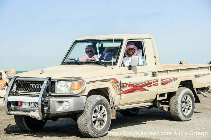 tres chicos omaníes en su coche junto al ferry masirah
