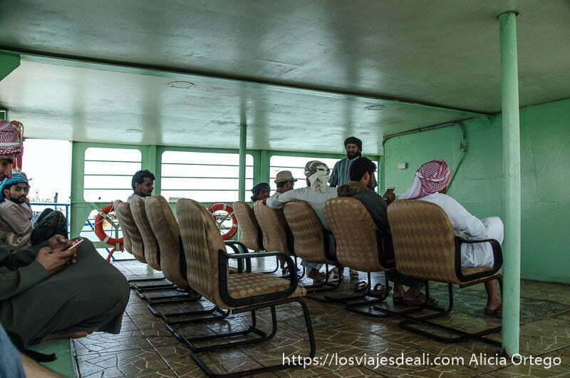 pasajeros del ferry de masirah sentados en sillas a la sombra