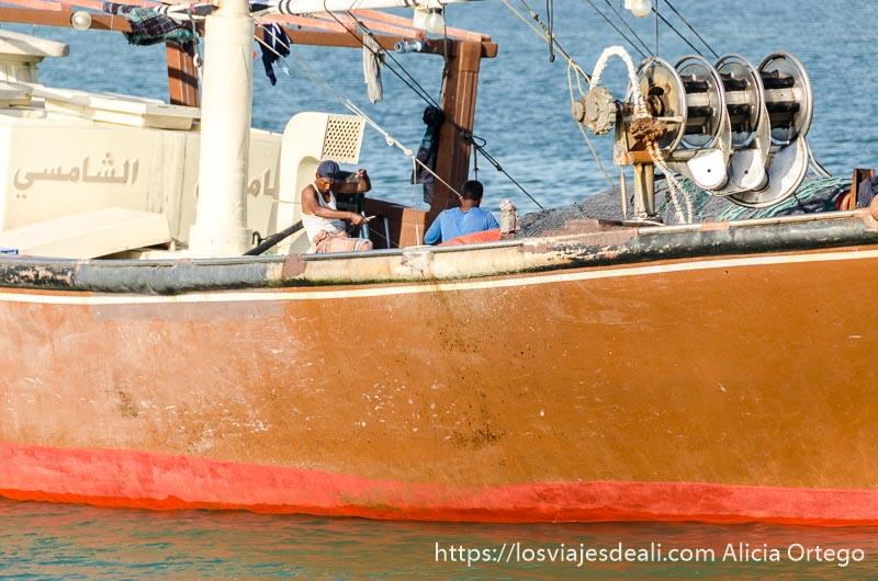 hombres faenando en su barco pintado de naranja en masirah
