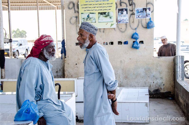 hombres en mercado de pescado en Omán