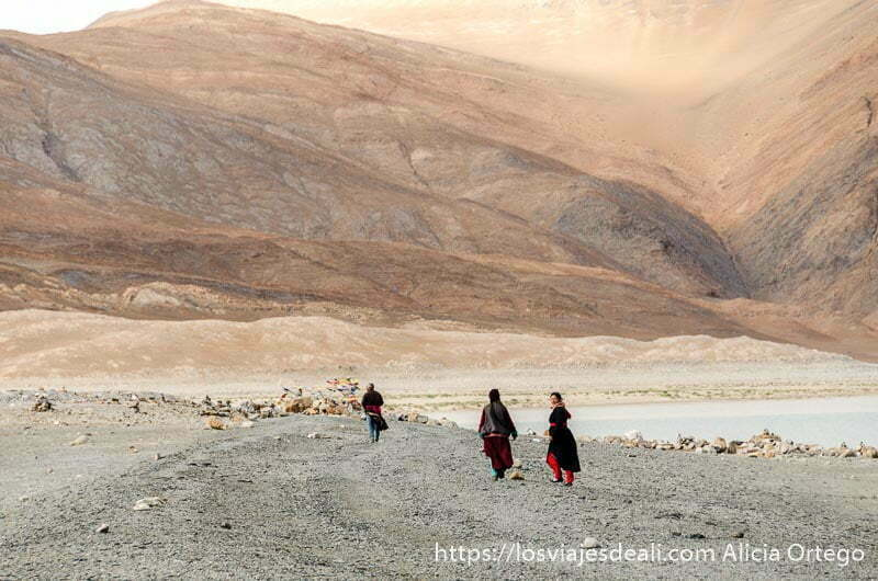 tres tibetanos andando hacia las montañas de colores marrones y naranjas junto al lago pangong