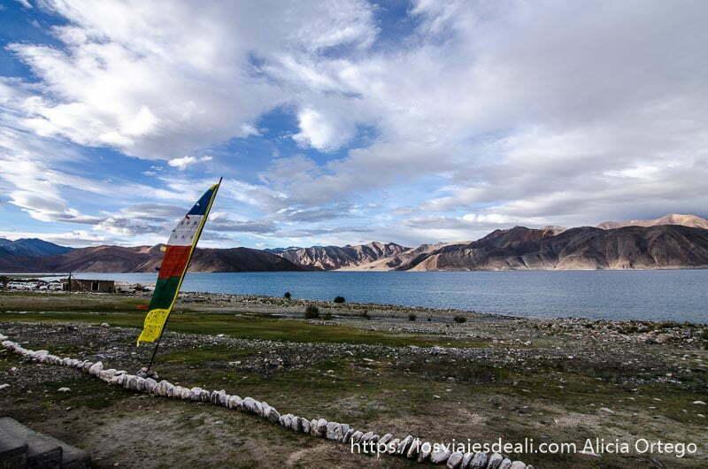 paisaje del lago pangong con montañas al fondo y unas banderas tibetanas