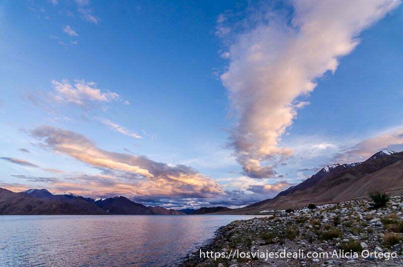 atardecer en el lago pangong con grandes nubes en forma de columna teñidas de rosa