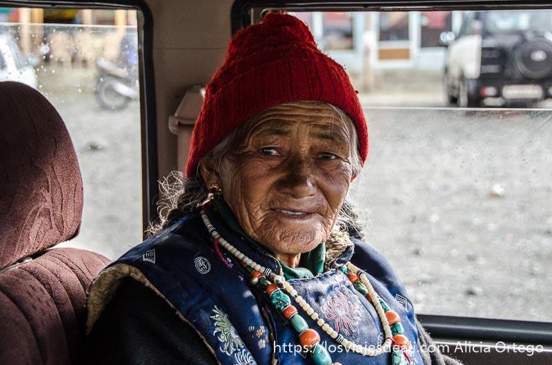 anciana de ladakh con trenzas, gorro de lana rojo y collares de turquesas junto al lago pangong