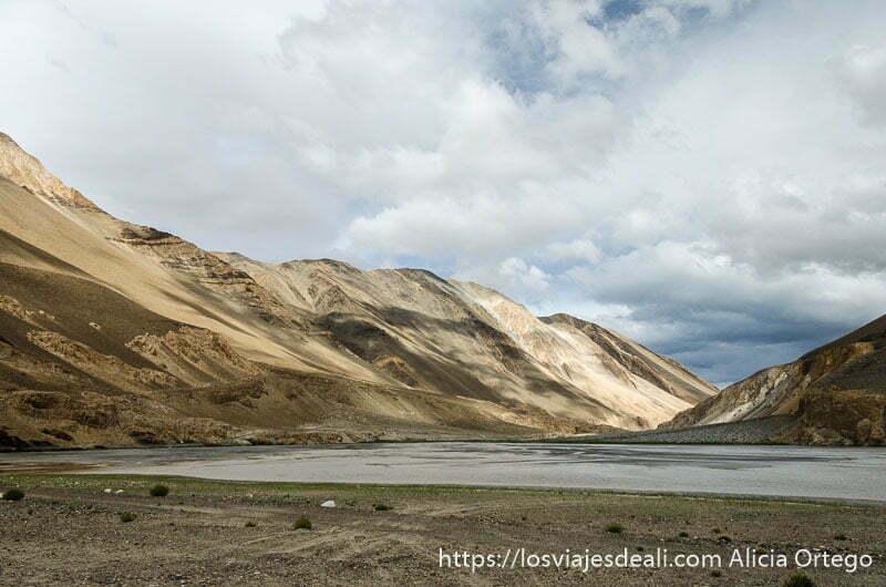 montañas de colores ocre y río con nubes y sol cerca del lago pangong