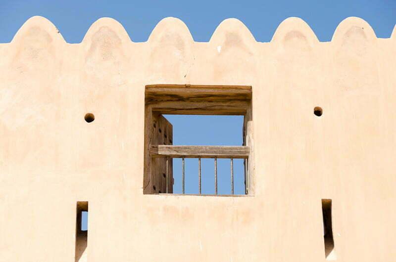 muro de adobe con almenas y ventana de madera recortándose en el cielo azul