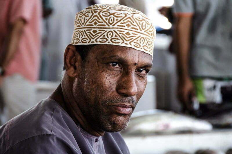 hombre moreno con ojos estrábicos y gorro bordado en el mercado de pescado en omán