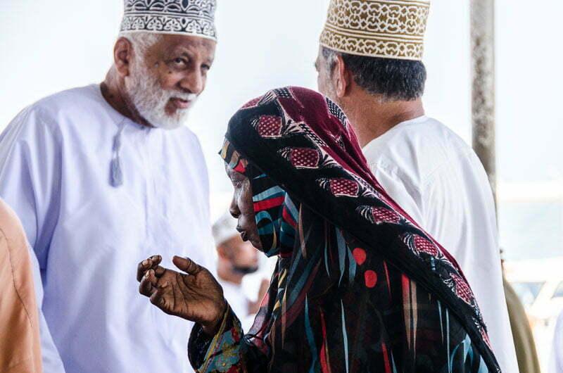mujer negra con velo en la cabeza entre los hombres del mercado de pescado en omán