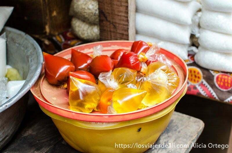barreño con bolsitas de plástico llenas de algo rojo y amarillo en el mercado de natitingou