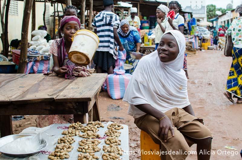chicas sentadas en un puesto del mercado de natitingou sonrientes