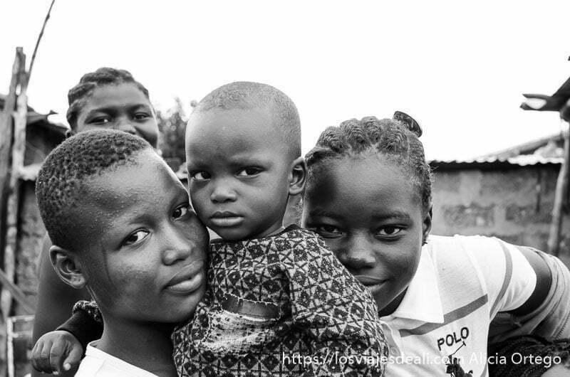 dos chicas con un niño en brazos  miran sonrientes a la cámara en natitingou