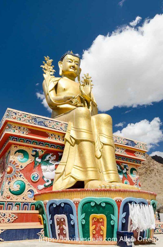 estatua gigante de buda revestida de oro bajo el cielo azul con nubes blancas valle del indo