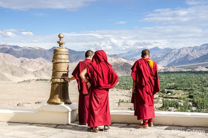monjes con hábito rojo asomados a la terraza del monasterio contemplan el valle del indo