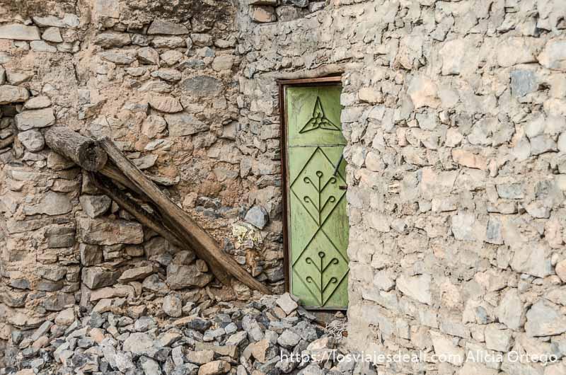 casa en ruinas con puerta de metal verde cordillera al hajar