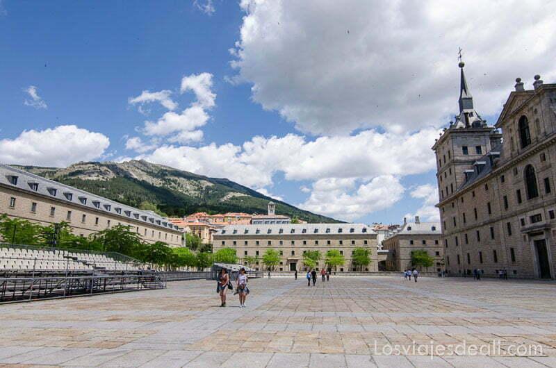 dos chicas andando por el patio del monasterio de el escorial y cielo con nubes