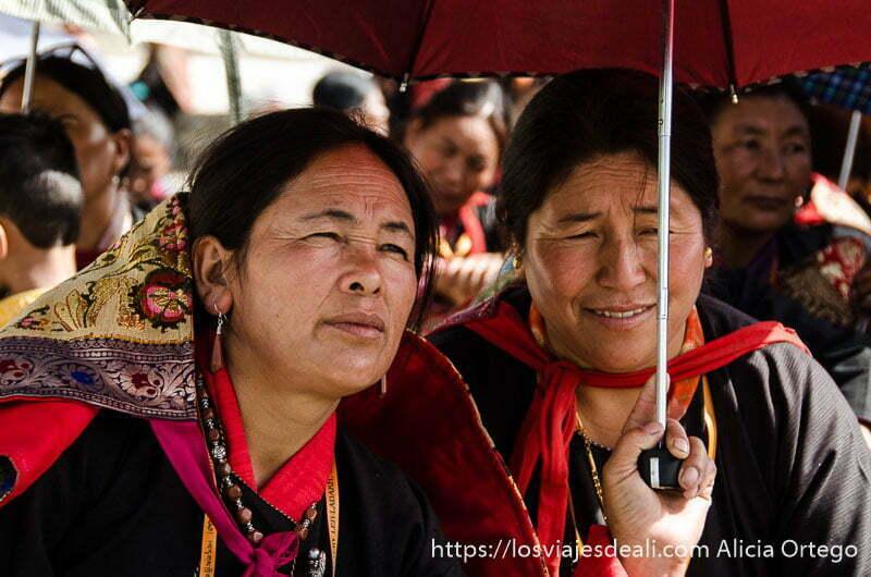 dos mujeres bajo un paraguas escuchando al dalai lama