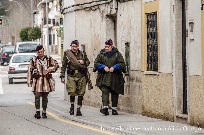 tres hombres caminan por una calle de morata de tajuña disfrazados de soldados de la guerra civil batalla del jarama