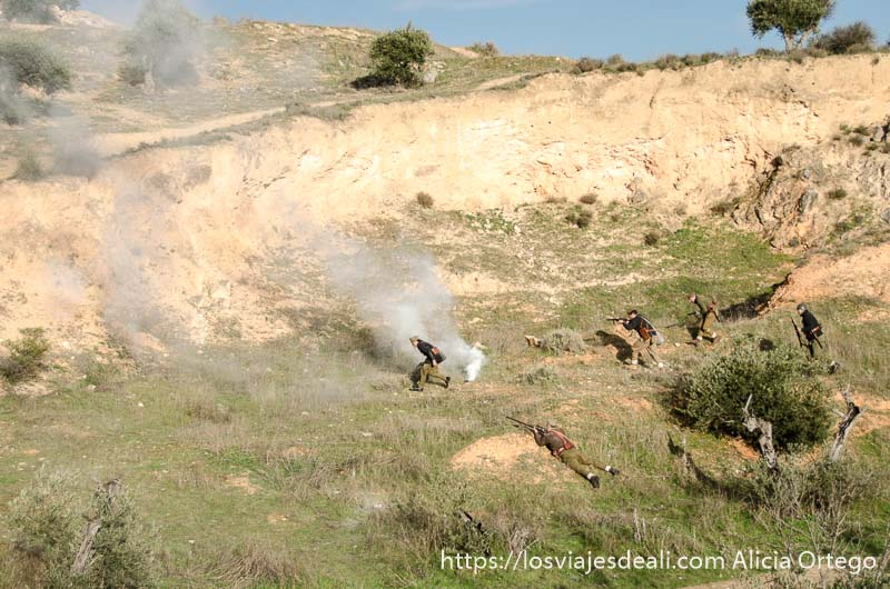 soldados corriendo por el campo con columna de humo en recreación de batalla del jarama
