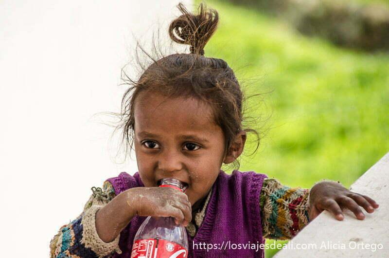 niña pequeña con botella de cocacola sonriente trekking cerca de leh