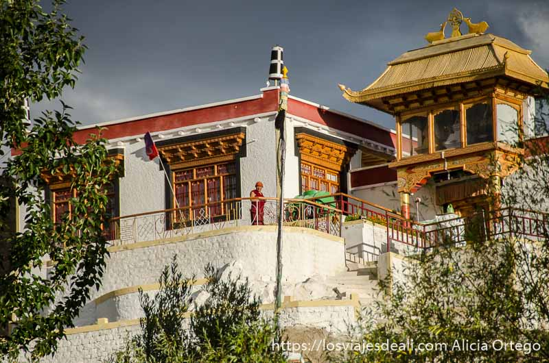 monje asomado al balcón de su monasterio con nubes de tormenta encima trekking cerca de leh
