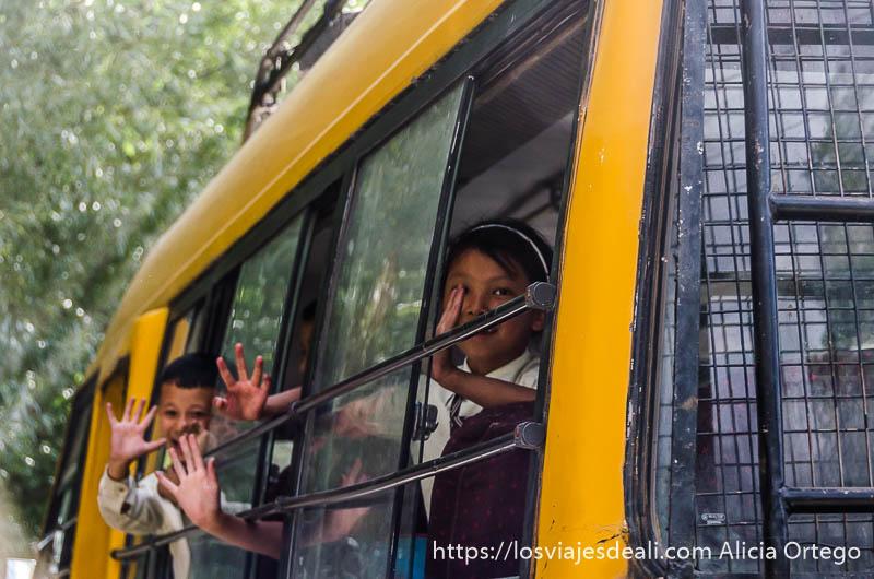 niños asomados a ventanas de bus escolar pintado de amarillo en trekking cerca de leh