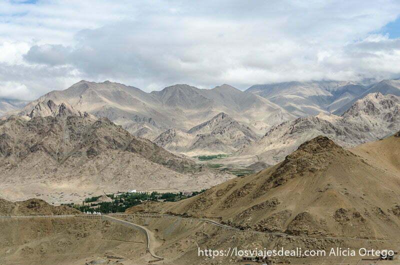 paisaje de montañas peladas y al fondo un oasis verde trekking cerca de leh