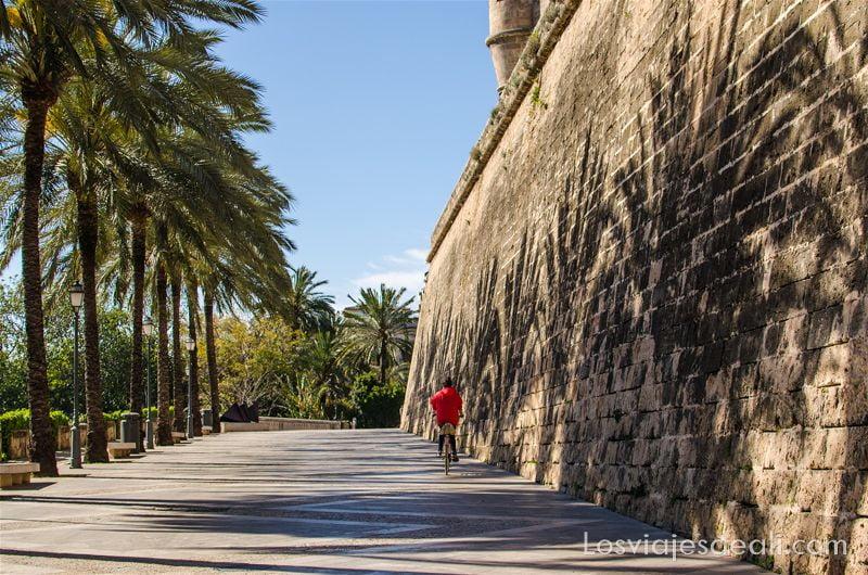 chica con chaqueta roja en bicicleta junto a muralla paseo fotográfico por palma de mallorca