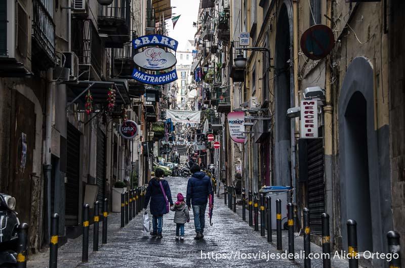 padres con su hija andando por el centro de calle estrecha paseos por nápoles