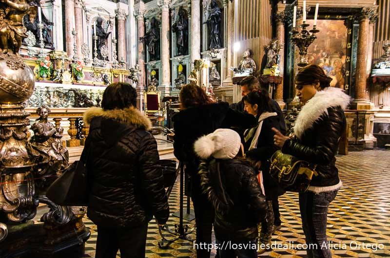 grupo de mujeres poniendo velas dentro de la catedral de nápoles