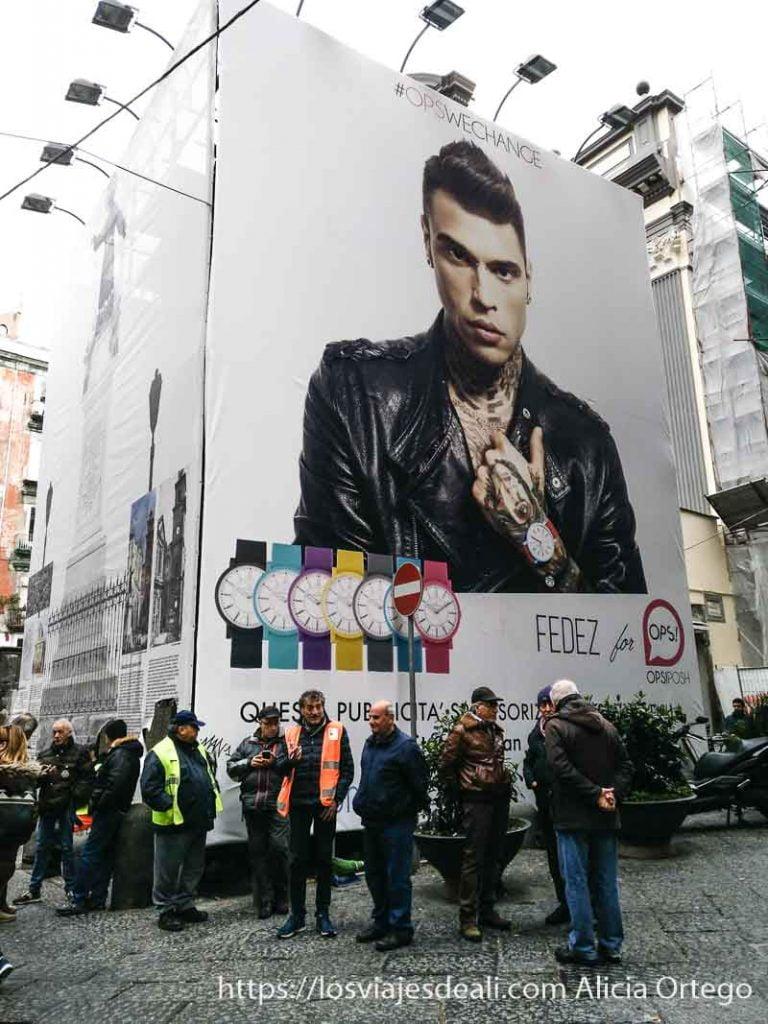 cartel de anuncio de relojes con hombres parados al lado en nápoles