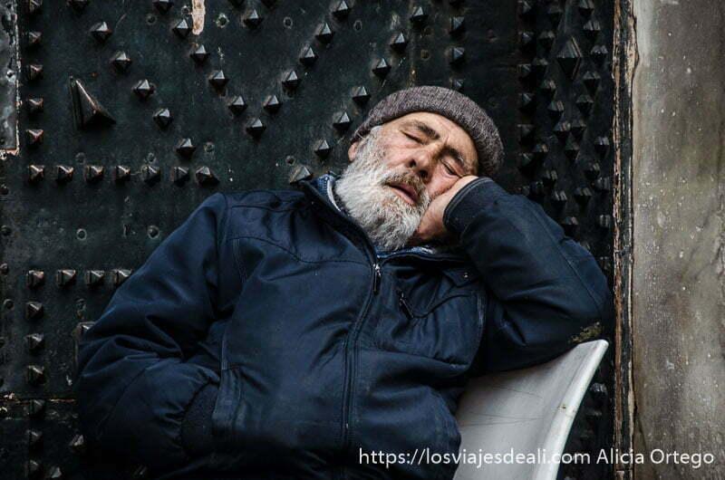hombre dormido con la mano apoyada en la mejilla en la puerta de una iglesia paseos por nápoles