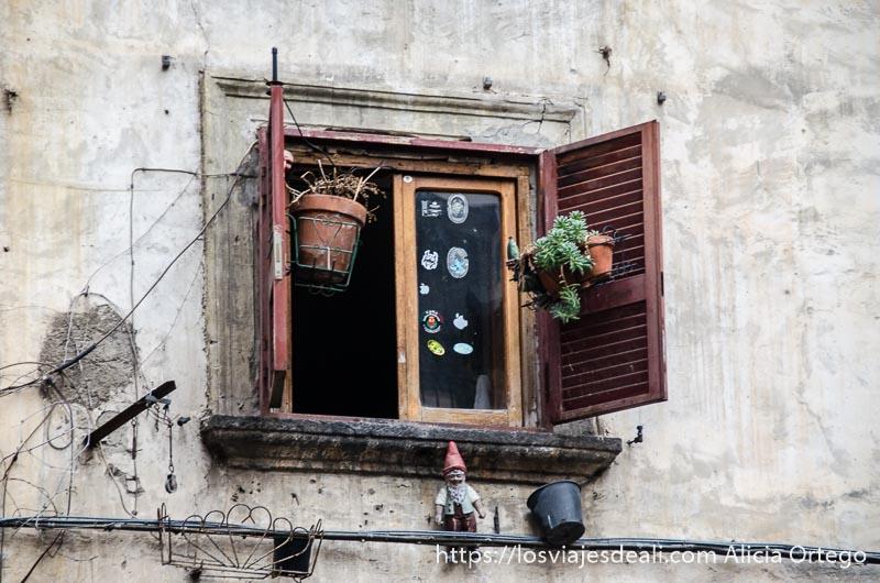 ventana con macetas y un enanito debajo paseos por nápoles