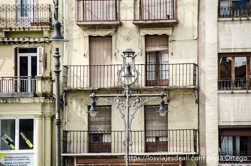 farola con tres brazos y fachada de balcones detrás pamplona