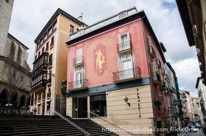 fachada de antigua farmacia pintada de rojo con figura griega en el centro pamplona