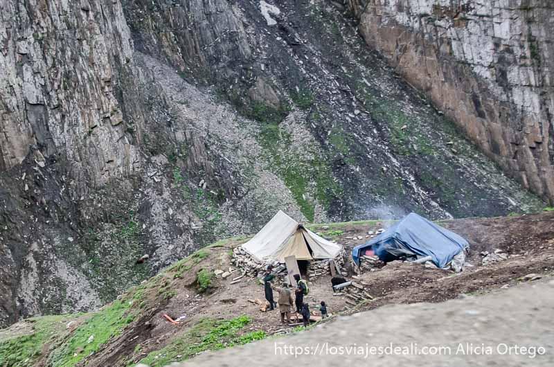 tiendas de campaña en un saliente junto a cortado que cae al río pueblos de cachemira