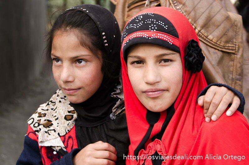 dos niñas con velo rojo y negro en uno de los pueblos de cachemira