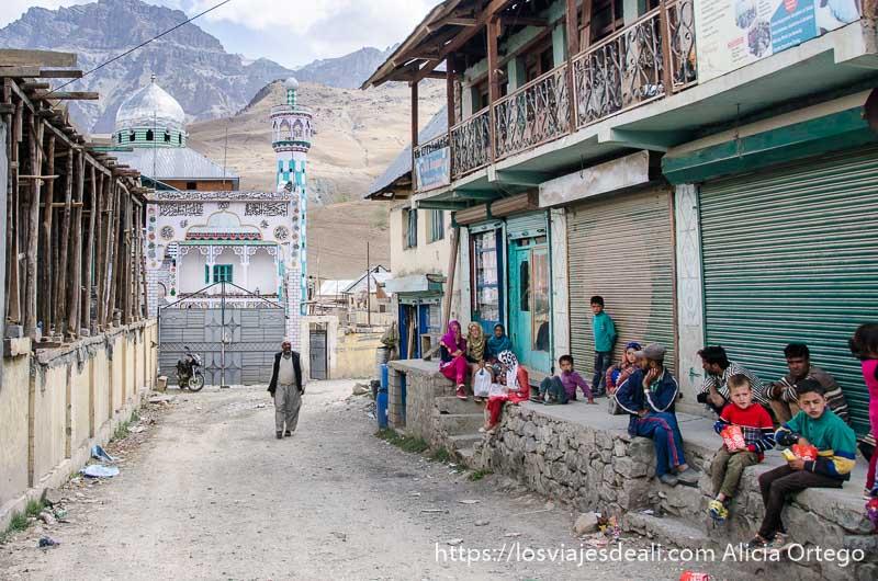 calle con mezquita al fondo y chicos sentados en un murete en uno de los pueblos de cachemira
