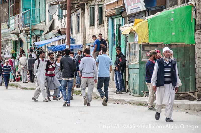 hombre mayores y jóvenes andando en grupos por la calle de uno de los pueblos de cachemira