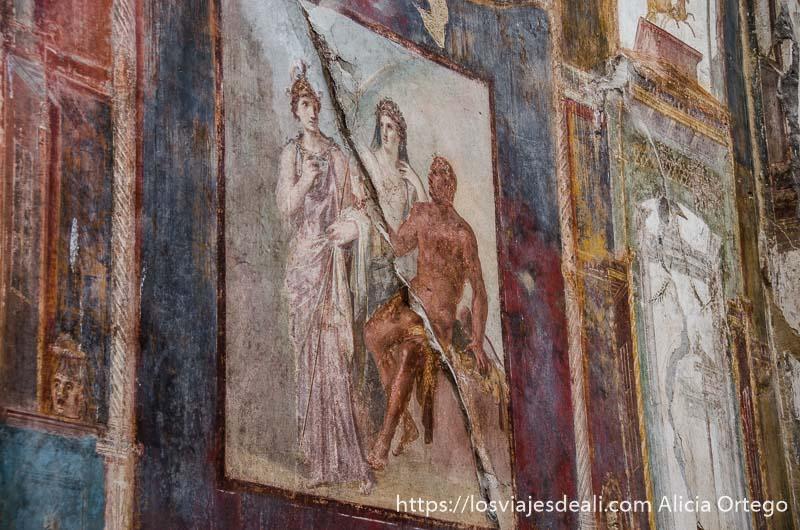 pintura al fresco con escena mitológica de dos mujeres y un hombre semidesnudo con vivos colores visita a herculano